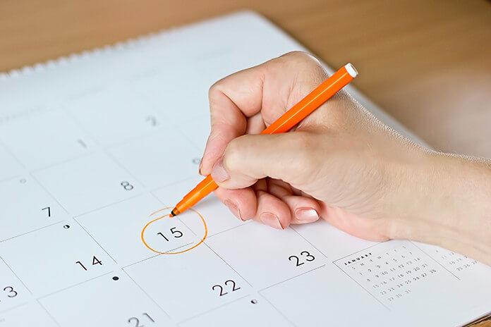 カレンダーにメモをする女性